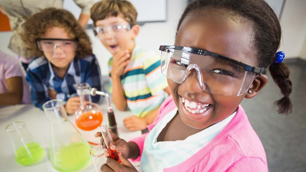 Girl smiling while holding a test tube with liquid inside. 2 other boys looking up at girl.  There are 2 beakers on the desk.
